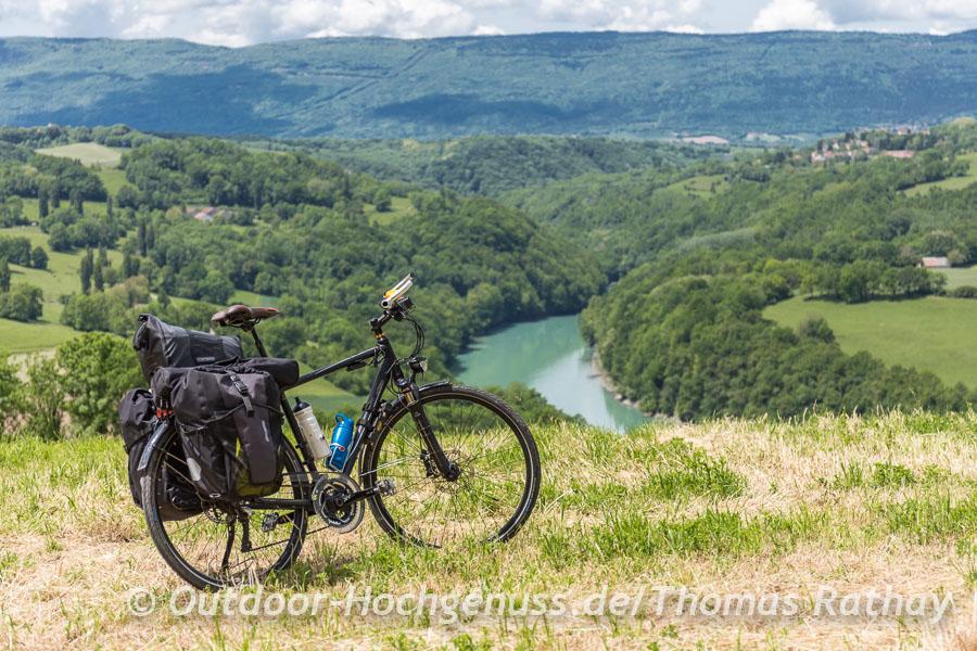 Blick auf die türkisfarbene Rhone umgeben von den grünen Hügeln des Juras