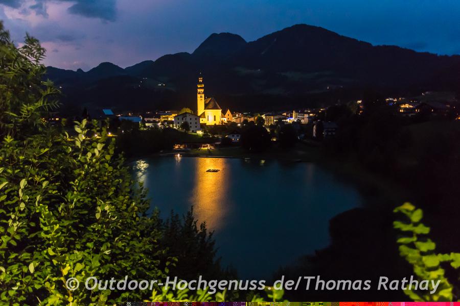 Abendlich illuminierte Kirche in Reith mit dem Badesee