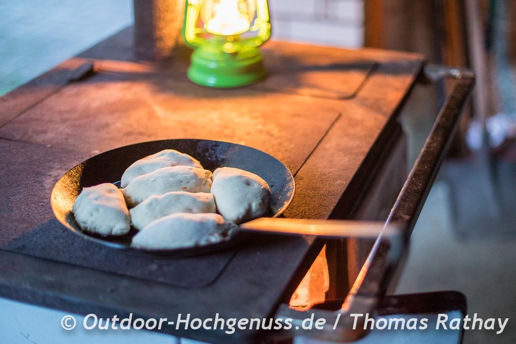 Empanadas mit Kümmelsalami, Zwiebel, Tomaten und Käse gefüllt aus der Gusspfanne von der Kochmaschine.