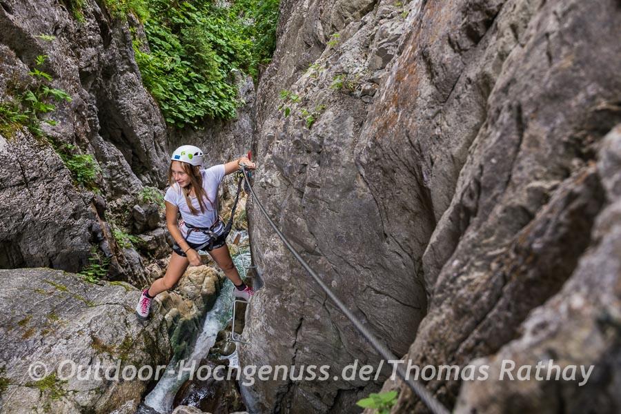 Metallklammern und Felsen bieten einen sicheren Tritt in diesem Klettersteig.